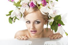 pretty blond with flower crown on head, she looks at left with an expression  - stock photo