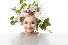 pretty blond with flower crown on head, she looks in to the lens and smiles - stock photo