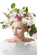 pretty blond with flower crown on head, her face is turned of three quarters. - stock photo