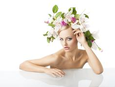 pretty blond with flower crown on head, looks in to the lens with actractive  - stock photo