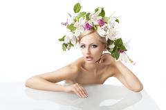 pretty blond with flower crown on head, she looks in to the lens with an expr - stock photo