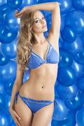 Swimsuit and balloons in blue, her left  arm is on the head Stock Photos