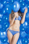 Stock Photo of swimsuit and balloons in blue, her face is behind one balloon