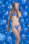 Swimsuit and balloons in blue, she has left hand on the face Stock Photos