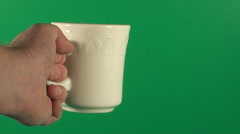 Hand Holding Coffee Mug In Front Of Green Screen Stock Footage