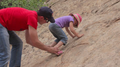 A father teaching his daughter to climb rocks Stock Footage