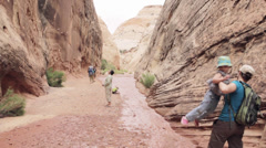 People in a deep desert slot canyon Stock Footage