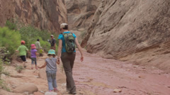 Family hiking in a deep desert slot canyon Stock Footage