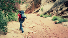 Father and baby walking in a deep desert slot canyon Stock Footage