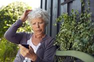 Stock Photo of elder woman reading text message on her cell phone