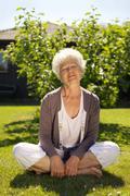 elder woman enjoying fresh air in garden - stock photo