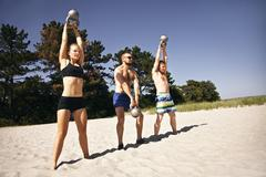 Group of athletes working out with kettle bell on beach Stock Photos