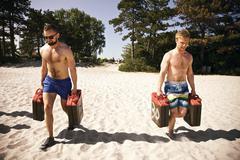 Tough athletes doing workout on beach with jerrycans Stock Photos