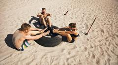 Group of athletes doing crossfit exercise routine on beach Stock Photos