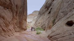 People hiking in a deep desert slot canyon Stock Footage