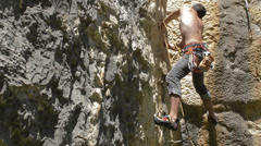 Rock climber rests and chalks up Stock Footage