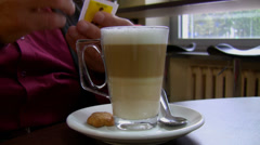 Pouring sugar into coffee latte - stock footage