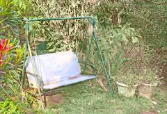 sunny corner resting place in overgrown garden - stock photo