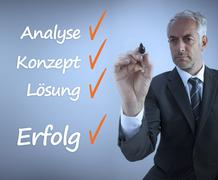 Attractive businessman writing a success checklist in german - stock photo