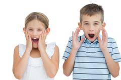 Brother and sister being shocked - stock photo