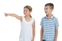 Young girl showing something to her brother - stock photo