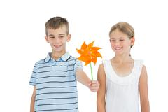 Brother and sister playing with pinwheel - stock photo
