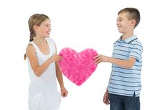 Stock Photo of Smiling children holding heart shaped soft toy