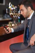 Handsome businessman sending a text while having a drink Stock Photos