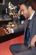 Stock Photo of Smiling businessman sending a text while having a drink