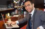 Stock Photo of Smiling businessman working on his laptop