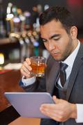 Serious businessman working on his tablet computer while having a whisky - stock photo