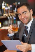 Cheerful businessman working on his tablet while having a whiskey - stock photo