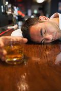 Unconscious businessman holding whiskey lying on a counter - stock photo