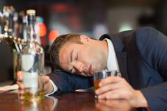Unconscious businessman holding whiskey glass lying on a counter - stock photo