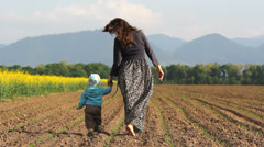 Little baby and young mother holding hands pass on spring soil Stock Footage