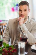 Stock Photo of Smiling handsome man waiting for his girlfriend at restaurant