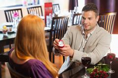 Handsome man proposing marriage to his pretty girlfriend Stock Photos