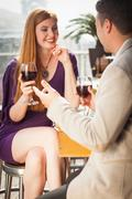 Stock Photo of Smiling woman having glass of wine with her boyfriend