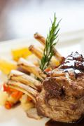 Delicious rack of lamb dish with rosemary sprig - stock photo