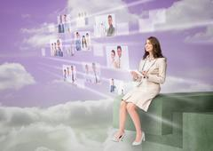 Cheerful businesswoman using futuristic interface - stock photo