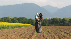Young woman with long hair and dress, hold in arms little baby walk, spring soil Stock Footage