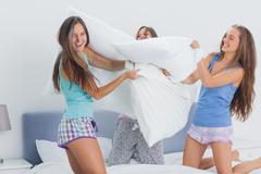 Friends having pillow fight - stock photo