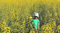 Alone sad baby in field with yellow rape flowers Stock Footage