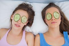 Friends lying in bed with cucumber slices on eyes - stock photo