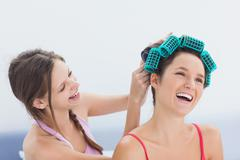 Stock Photo of Girl fixing her friends hair rollers