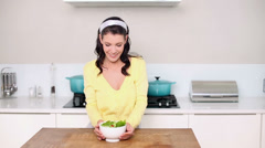 Beautiful brunette picking up a bowl of salad - stock footage
