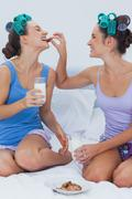 Pretty friends sitting in bed having milks and cookies Stock Photos