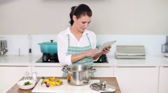 Beautiful brunette following a recipe on her tablet pc while making dinner Stock Footage