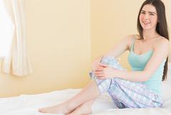 Stock Photo of Happy young girl looking at camera and sitting on her bed