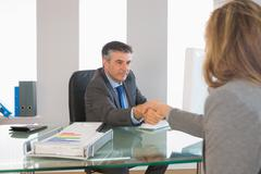 Stock Photo of Serious businessman shaking the hand of a interviewee